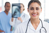 Smiling doctor standing in a bright hospital