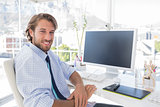 Smiling designer sitting at his desk
