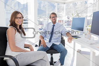 Pair of designers sitting in office