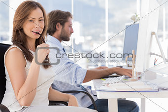 Woman biting her glasses with colleague working behind