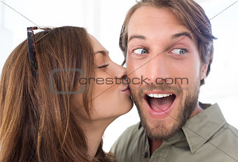 Woman kissing man with beard on the cheek