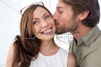 Man kissing pretty woman on the cheek