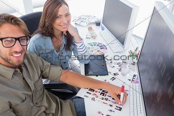 Two happy photo editors working with contact sheets