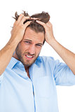 Tanned stressed man holding his hair