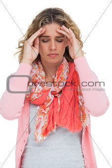 Blonde girl touching her temples because of a headache