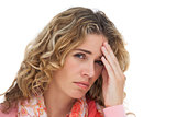 Blonde woman suffering with headache and holding her head