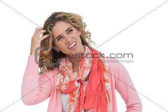 Blonde woman scratching her head and smiling