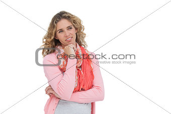 Blonde thoughtful woman smiling while touching her chin