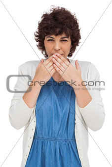 Astonished brunette woman putting hands on mouth