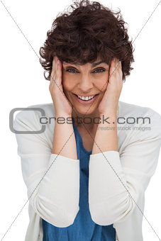 Astonished brunette woman holding her head between hands