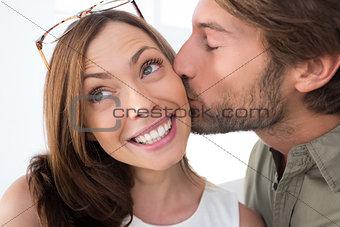 Man giving pretty woman kiss on the cheek