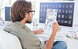 Photo editor examining contact sheet