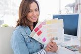 Smiling interior designer holding up colour samples