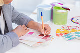 Pretty interior designer drawing on colour samples