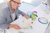 Smiling blonde interior designer holding colour charts