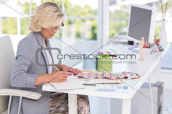 Blonde interior designer working on her desk