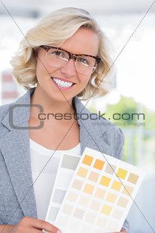 Beautiful interior designer holding up colour samples