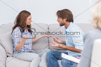 Couple arguing while the therapist is listening to them