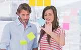 Woman showing the sticky note to her colleague