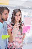 Woman showing sticky note to her colleague