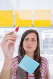 Young woman writing on sticky note