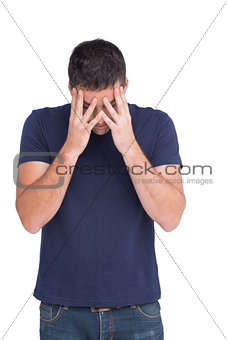 Upset man standing with his head in hands