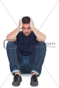 Sitting upset man with head between hands