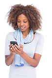 Smiling woman typing a text message on her smartphone