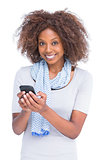 Smiling woman looking at camera and typing a text message