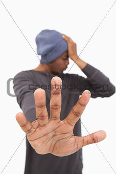 Man in beanie hat holding hand out to stop