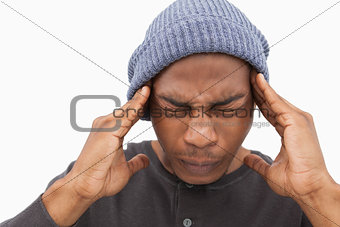 Man in beanie hat wincing with pain of headache
