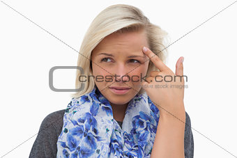 Anxious blonde pointing to forehead