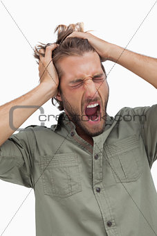 Tired man yawning and running fingers through hair