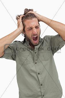 Sleepy man yawning and running fingers through hair