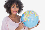 Happy woman pointing to globe