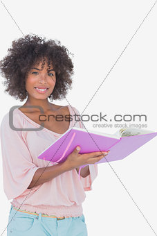 Beautiful woman holding photo album and smiling