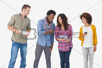 Four stylish friends looking at tablet and holding phones