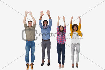 Four stylish friends smiling at the camera and jumping