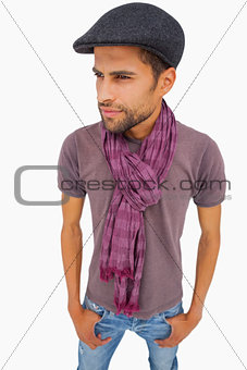 Thougthful man wearing peaked cap and scarf