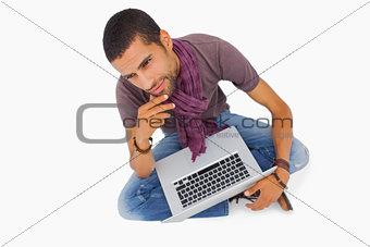 Thoughtful man sitting on floor using laptop