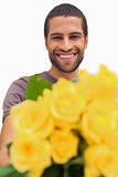 Handsome man offering bunch of yellow roses