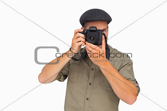 Man in peaked cap taking photo