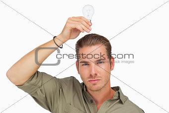 Man holding light bulb above his head