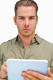 Serious man using tablet pc looking at camera