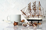 Souvenir yacht, cup and candies on white background