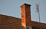 Orange roof tiles, chimney and old analog TV antenna