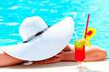 girl in a wide white hat resting in the pool