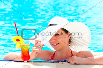 happy girl with a cocktail at the pool holding a hat hand