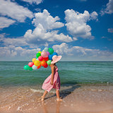Young woman walking on the beach with colored balloons / Travel