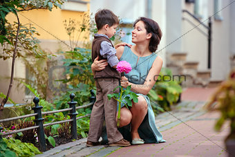 Little boy giving flower to his mom in city street